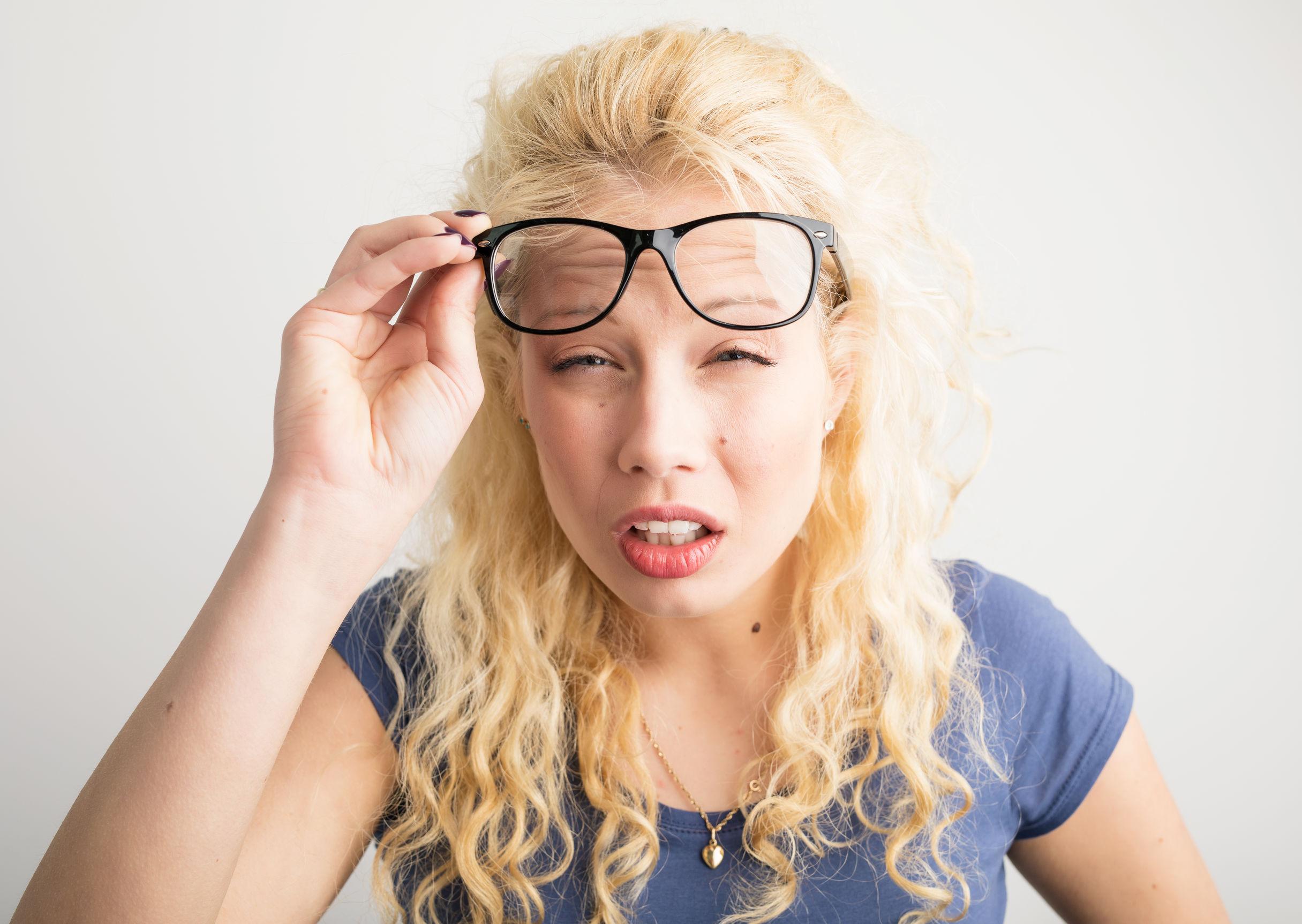 Jeune femme ne pouvant pas voir avec ses lunettes levées